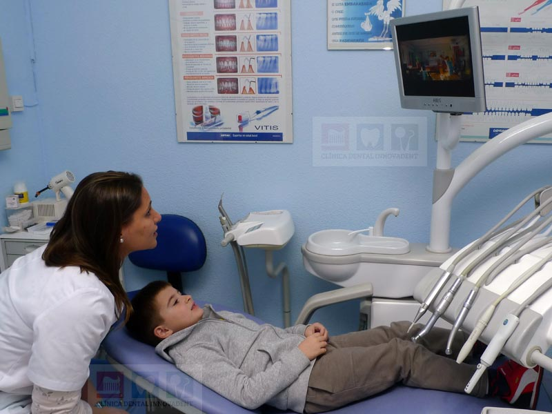 Odontopediatra de Innovadent elegiendo junto a un niño los dibujos que este quiere ver